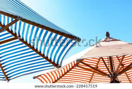 Colorful striped beach umbrellas against a cyan sky. View from underneath looking up. Copy space. - stock photo