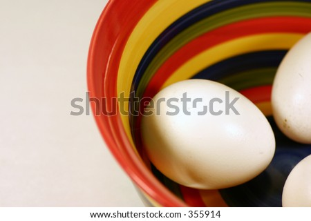 Colorful striped bowl with three eggs inside. - stock photo