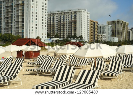 Colorful striped lounge chairs and umbrellas along the shoreline in beautiful Miami Beach. - stock photo