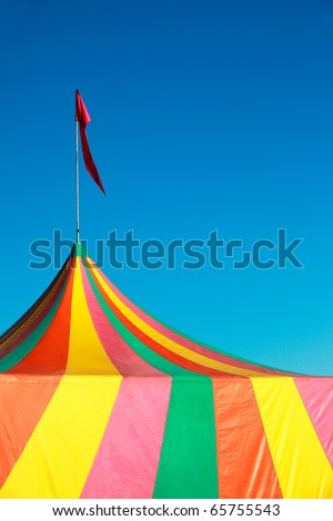 Colorful stripes on a big top tent at a fair against a clear blue sky.
