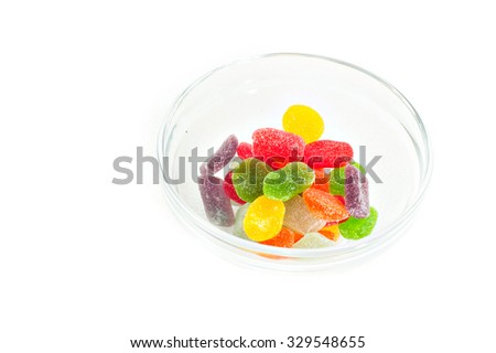 Colorful sugar pastilles candy in a glass bowl with white background.