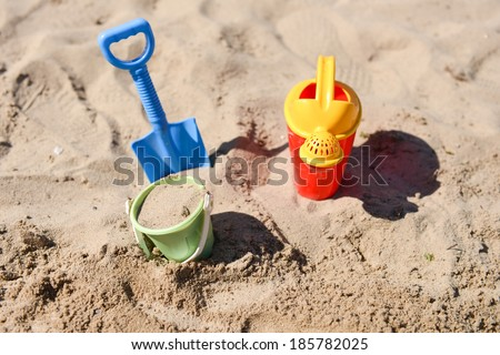 Colorful summer beach toys, bucket, sprinkler and shovel on sand on a sunny day - stock photo