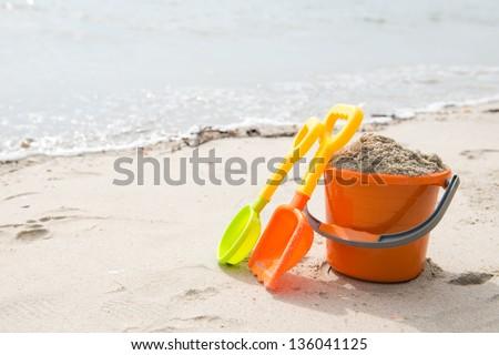 Colorful summer beach toys on sandy beach - stock photo