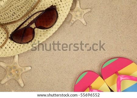 Colorful summer beachwear, flip flops, hat, sunglasses and starfish on sand beach. - stock photo