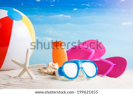 Colorful summer flip flops, lotion, diving glasses and starfish on sand beach - concept - stock photo