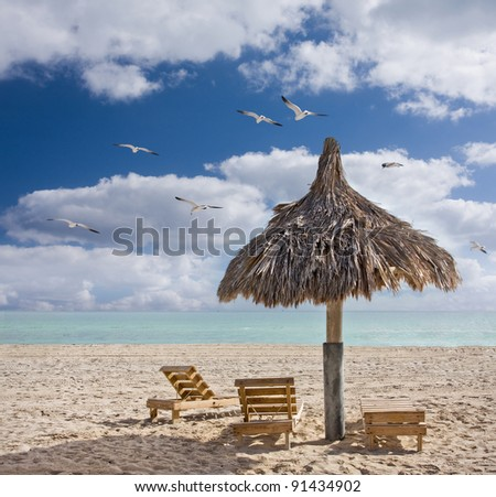 Colorful summer image of wooden beach chairs and a cabana in Miami Beach Florida during early sunny morning with pristine sand and waters of Atlantic Ocean and blue sky with clouds. Copyspace. - stock photo