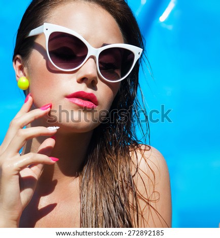 Colorful summer portrait of young attractive brunette woman wearing sunglasses at the swimming pool