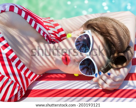 Colorful summer portrait of young attractive woman wearing sunglasses lying down by the swimming pool - stock photo