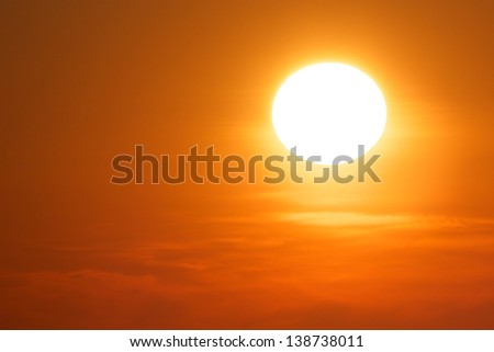 Colorful sun in a clear orange sky with some clouds - stock photo