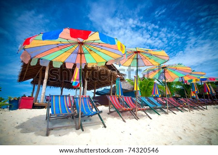 Colorful sun parasols and sundeck chairs on beautiful white sandy beach in the tropics.
