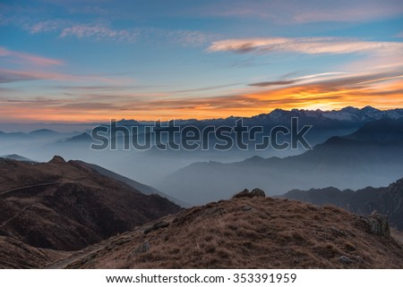Colorful sunlight behind majestic mountain peaks of the Italian - French Alps, viewed from distant. Fog and mist covering the valleys below, autumnal landscape, cold feeling. - stock photo
