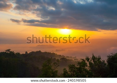 Colorful sunrise over jungle with Merapi volcano behind and Borobudur temple, Indoneisa - stock photo