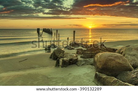 Colorful sunrise with old broken wharf, Baltic Sea. Image slightly toned for inspiration of retro style - stock photo