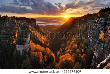 Colorful sunset above the misty deep valley during the autumn in national park Bohemian Switzerland - stock photo