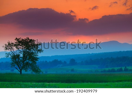 Colorful sunset and clouds over Mt. Mansfield in Stowe Vermont, USA - stock photo