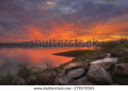 Colorful sunset at the rocks and Silhouettes landscape view sunset Water reflection,rayong thailand