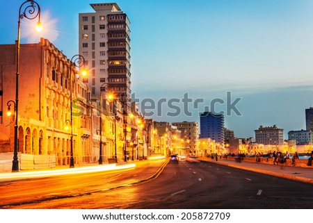Colorful sunset in Old Havana with  the street lights of El Malecon and light trails from the passing cars - stock photo