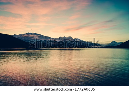Colorful sunset in Southeast Alaska as seen by ferry. - stock photo