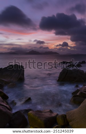 Colorful sunset long exposure with view to Praslin from La Digue, Seychelles with granite rocks in the foreground - stock photo