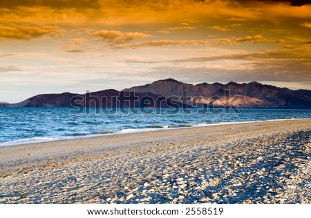 Colorful sunset on the sandy beach with mountainous islands in the background. - stock photo