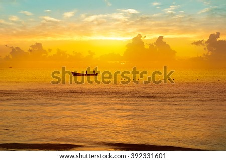 Colorful sunset on the tropical beach with beautiful sky, clouds and soft waves. Photo from Playa del Carmen, Yucatan, Mexico.