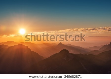 colorful sunset on top of austrian mountain alps - stock photo