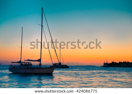 Colorful sunset over bay with silhouette sailboats.  Key West Florida - stock photo
