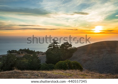 Colorful sunset over California ocean, rolling hills. Vibrant sunset over Pacific Ocean. Sun rays on rolling hills and trees of Mount Tamalpais.