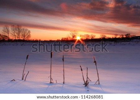 Colorful sunset over frozen lake - stock photo