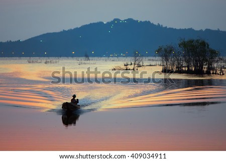 Colorful sunset over the lake with silhouette fisherman on boat. - stock photo