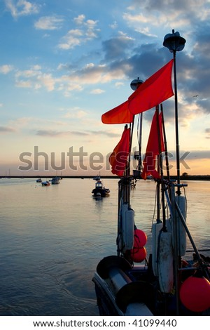 colorful sunset over the stern of a fishing boat - stock photo