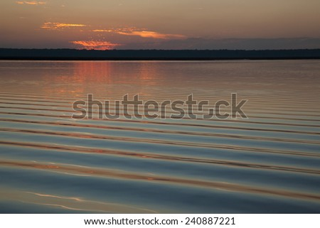 Colorful sunset over the water of a river - stock photo