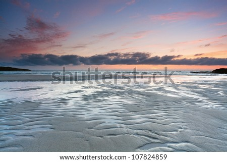 Colorful sunset over tidal beach of Tangasdale, Isle of Barra, Outer Hebrides, Scotland. - stock photo