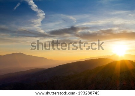 Colorful sunset rays over distant mountains in Joshua Tree National Park, California - stock photo
