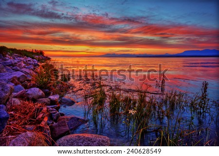 Colorful sunset with intriguing rocky riverside and green grass - stock photo