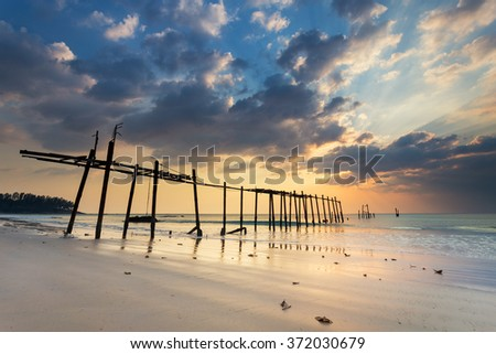 Colorful sunset with some clouds during low tide on Pilai beach in Phang Nga province in Thailand - stock photo