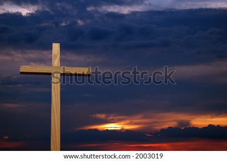 Colorful sunset with wooden cross in the foreground.