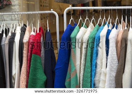 Colorful sweaters on clothes rack