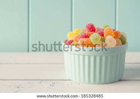 Colorful sweet jellies with sugar in a turquoise classic white-ware baking bowl on a white wooden table with a robin egg blue background. Vintage look. - stock photo