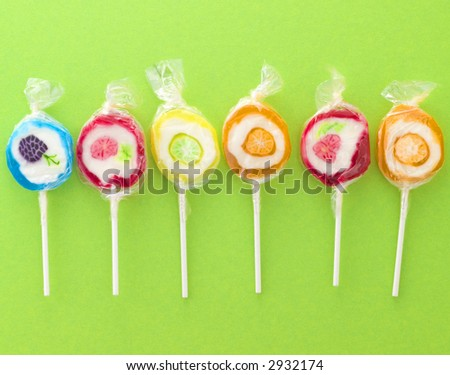 colorful sweet lollipops on a green background - stock photo
