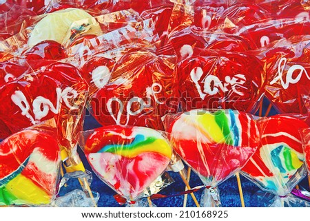 Colorful sweets, candies and lollipops with word love at street market - stock photo
