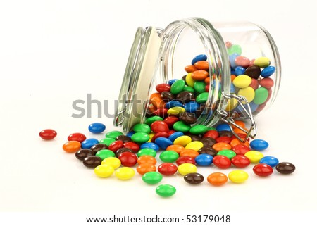 colorful sweets in a glass jar on a white background