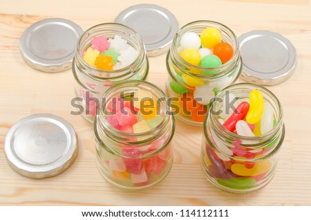 Colorful sweets in the four clear glass jars arranged parallelogram on wooden board