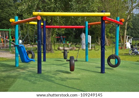 Colorful swings at playground in public park - stock photo