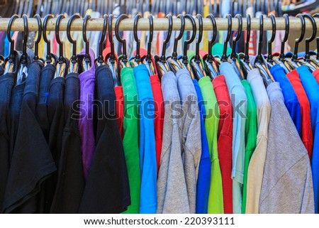 Colorful t-shirt on hangers in street market thailand - stock photo