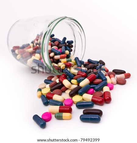 colorful tablets and capsules in glass container - stock photo