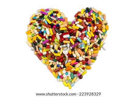 colorful tablets arranged in heart shape, symbol photo for heart disease, medication and pharmaceuticals - stock photo