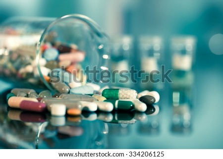 Colorful tablets with capsules and pills on blue background - stock photo