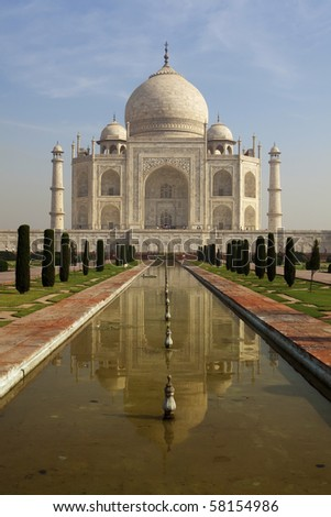 Colorful Taj Mahal from the southern entrance reflected in the pond. - stock photo