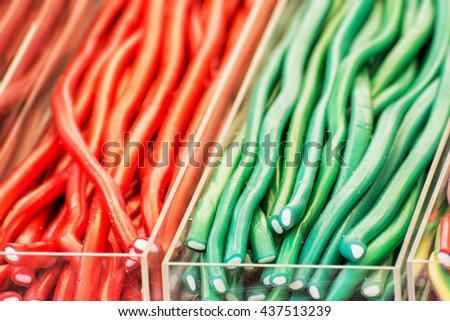 Colorful tasty licorice candies in plastic containers. Sweet delight. Vibrant colors. Sweetmeats scene. Confectionery in the shop. - stock photo
